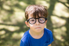 Young boy in spectacles. Portrait of cute young boy in spectacles at park Royalty Free Stock Images