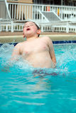 Young boy splashing into pool Stock Images