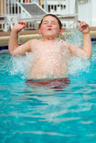 Young boy splashing into pool Stock Photos