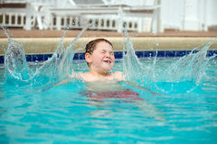 Young boy splashing into pool Royalty Free Stock Image