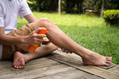 Young boy spraying insect repellents on his leg with spray bott stock photo