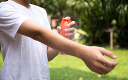 Young boy spraying insect repellents on skin with spray bottle Stock Images