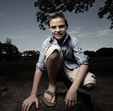 Young boy squatting and smiling Royalty Free Stock Photos