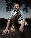 Young boy squatting and smiling Stock Photo