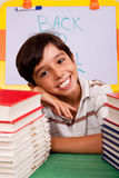 Young boy with stack of books Royalty Free Stock Images
