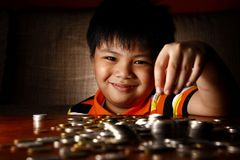 Young Boy Stacking or Piling Coins Royalty Free Stock Images