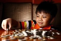 Young Boy Stacking or Piling Coins Royalty Free Stock Image