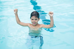 Young boy standing with arms up in pool Royalty Free Stock Image