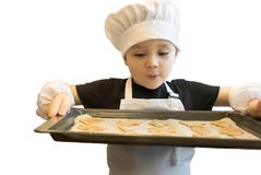 Young boy standing with baking tray full of gingerbread cookies, cutted with the help of different molds. Christmas Stock Images