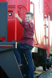 Young boy standing on a caboose Stock Photo