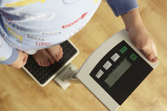 Young boy standing on digital scales cropped waist down Stock Images