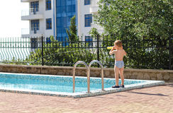 Young boy standing at the edge of a pool Royalty Free Stock Photos