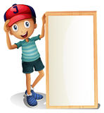 A young boy standing beside an empty signboard Royalty Free Stock Photo