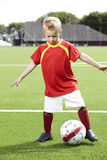 Young boy standing on a football field Royalty Free Stock Photo