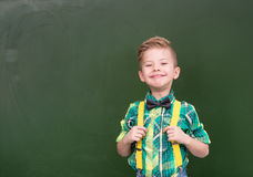 Young boy standing near empty green chalkboard Royalty Free Stock Photos