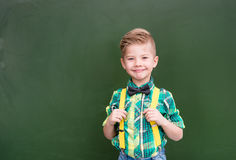 Young boy standing near empty green chalkboard Royalty Free Stock Photo