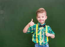 Young boy standing near empty green chalkboard and showing thumb Stock Image