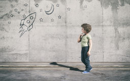 The young boy standing next to grey wall. Curious kid looks to a rocket in space painted on wall. This is a 3d render illustration Royalty Free Stock Image