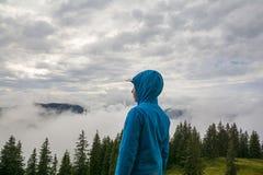 Young boy standing on the peak, Tirol, Austria. Young boy standing on the peak and looking to the misty landscape, in the Kitzbuhel mountains, Tirol, Austria Stock Photography