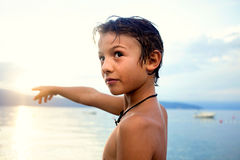 Young boy standing pointing into the sky in front of sea Royalty Free Stock Photos