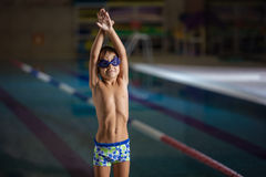 Young boy standing on side of swimming pool Royalty Free Stock Image