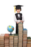 Young boy is standing at stacks of books Royalty Free Stock Images