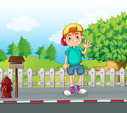 A young boy standing at the streetside near the wooden mailbox Royalty Free Stock Photo