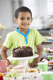 Young Boy Standing By Table Laid With Birthday Party Food Royalty Free Stock Photos