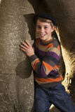 Young boy standing beside tree trunk Stock Photos