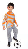 Young Boy Stands with Foot on Football Royalty Free Stock Image