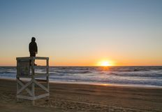 Young Boy Watches Sunrise From Lifeguard Chair stock image