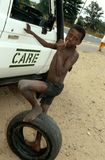A young boy stands next to a CARE van in Rwanda. Stock Photo