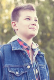 Young boy stands park meadow sunny day, jeans jacket, shirt looks into distance. A young boy stands in a park on a meadow on a sunny day, jeans jacket, shirt Stock Photo