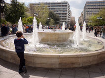 Young boy stare the fountain. ATHENS.GREECE - MARCH 26,2016: Young boy stare at the fountain and people walk around in Syntagma square in Athens,Greece royalty free stock image