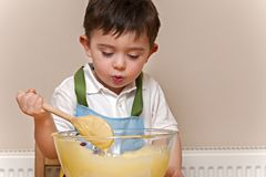 Young boy stirring cake mix in a glass bowl Royalty Free Stock Photo