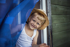 Young boy with straw hat smiling. Outdoor portrait:  Young boy with straw hat smiling Royalty Free Stock Photography