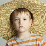Young boy with straw hat. Studio portrait of funny child Royalty Free Stock Images
