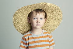 Young boy with straw hat. Studio portrait of funny child Royalty Free Stock Image