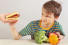 Young boy in a striped shirt at the table refuses hamburger in favor of healthy diet. On a white background stock images
