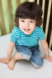 A young boy in a striped t-shirt and jeans. Sitting in a crib royalty free stock image