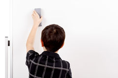 Young boy student and whiteboard. Young boy student in a classroom erasing white board Royalty Free Stock Photography