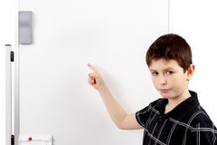 Young boy student and whiteboard. Young boy student in a classroom showing on a empty white board Stock Images
