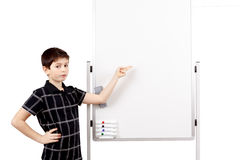 Young boy student and whiteboard. Young boy student in a classroom showing on a empty white board Royalty Free Stock Images