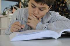 Young boy studying. Child is writing answers into her workbook stock photos