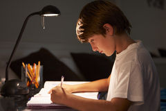 Young Boy Studying At Desk In Bedroom In Evening Royalty Free Stock Photos