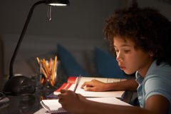 Young Boy Studying At Desk In Bedroom In Evening Stock Images