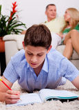 Young boy studying with family in the background Royalty Free Stock Photos