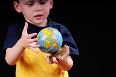Young boy studying globe. Young child looking at world globe Royalty Free Stock Images