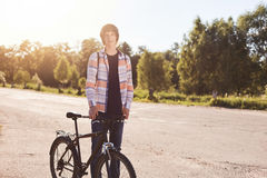 Young boy with stylish hairstyle wearing shirt and jeans standing with bicycle having trip admiring beautiful nature. Handsome cyc Royalty Free Stock Image