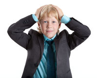 Young boy in suit clasped his head, looking at camera, isolated white background Royalty Free Stock Photography